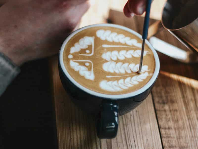 person holding black ceramic mug with coffee