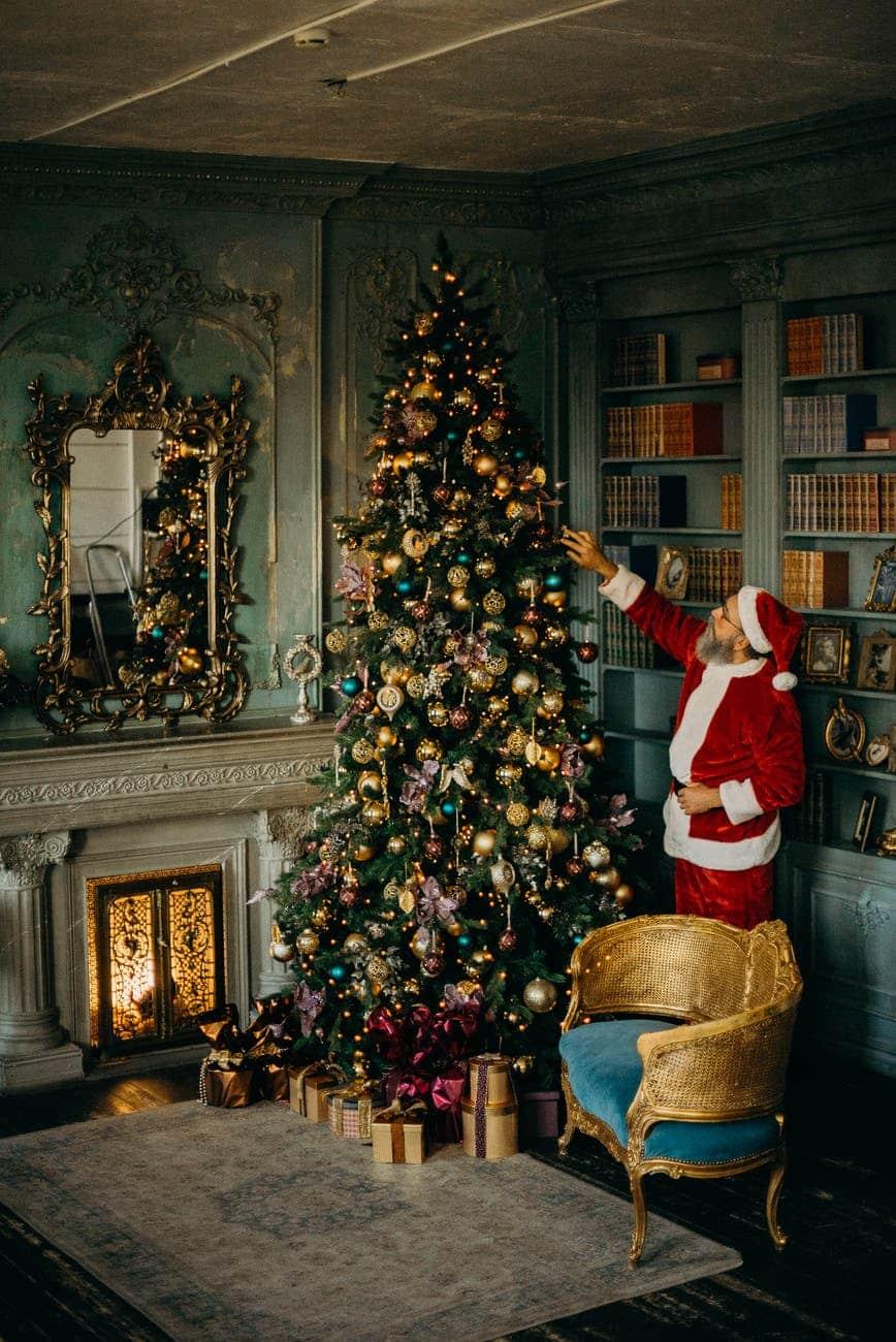 man standing beside christmas tree