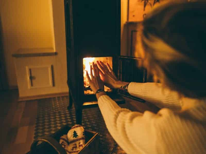 woman wearing white long sleeved try to get heat at fireplace