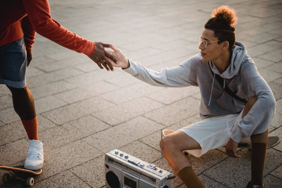 trendy multiracial skaters greeting each other during training on street